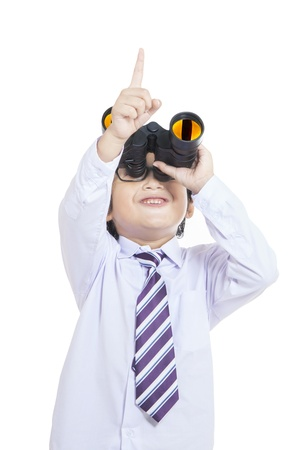 Cheerful business kid holding binoculars on white background photo