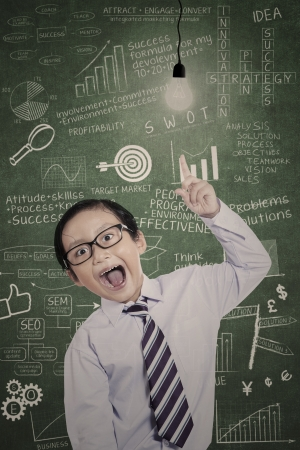 light classroom: Little businessman pointing at lit bulb in classroom Stock Photo