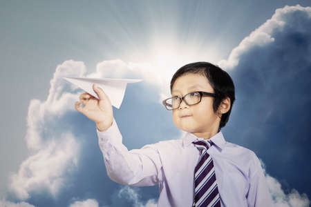 Little businessman with paper plane outdoor under cloudy sky photo