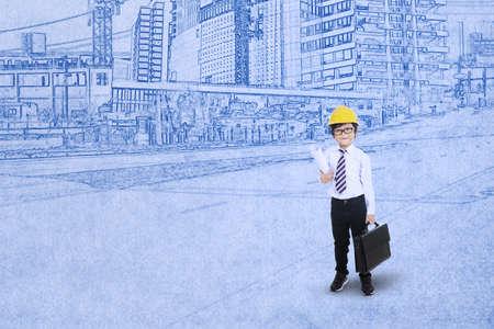 hispanic boy: Little engineer standing with blueprint background