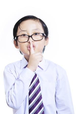 discreto: Kid de negocios que hace la expresi�n del silencio en el fondo blanco Foto de archivo