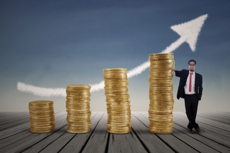 Asian businessman standing next to gold coins chart with blue sky background photo