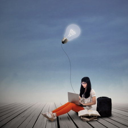 Asian female student is working on laptop under lit bulb outdoor Stock Photo - 21991852