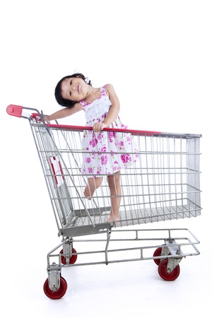 Cute little girl inside shopping trolley on white background photo