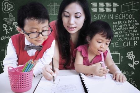 proud: Beautiful female teacher help children write letters in class