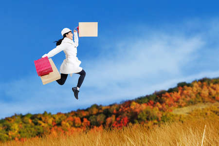 Autumn shopping woman jumping over grass photo