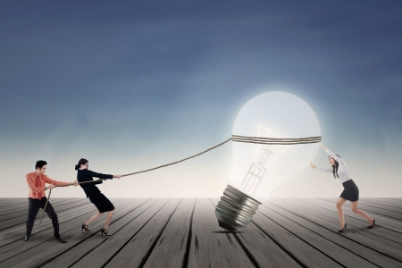 pulling rope: Business teamwork is pulling a bright lamp outdoor Stock Photo