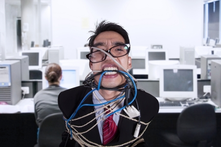 Close-up angry businessman tied in rope and cable at office photo