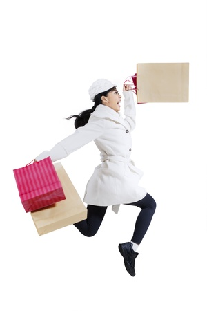 Happy shopper woman with shopping bags jumping isolated on white background photo