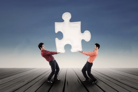 Two businessmen bring a puzzle together over blue sky background photo