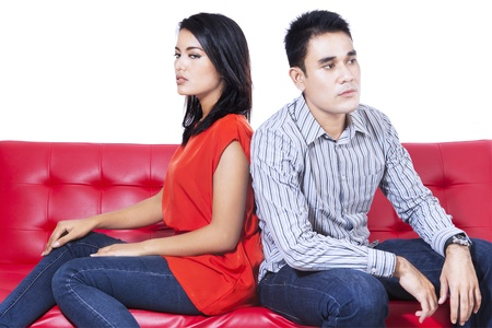 couple fight: Angry couple sitting back to back on the red sofa over white background Stock Photo