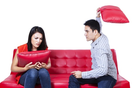 Asian young couple fighting with pillows on red sofa Stock Photo - 22114524