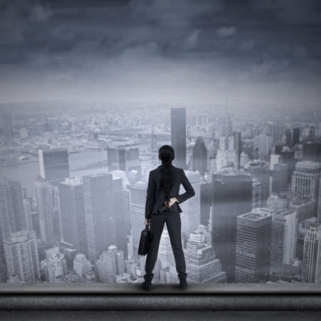 Businesswoman looking for a future and standing on the top of a skyscraper with cityscape photo