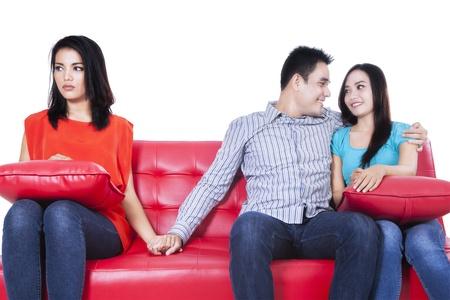 Mooie jonge vrouw hand in hand met man zit in de buurt van zijn vriendin