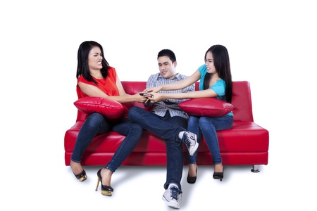 Young man and two woman are fighting for remote control isolated on white background photo