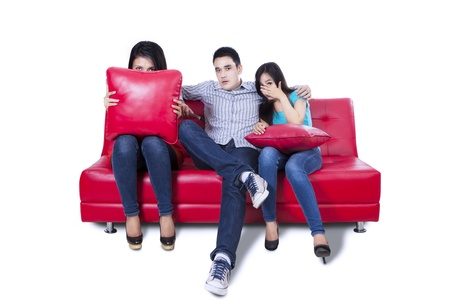 Friends - a man an two woman watching a scary movie in TV isolated on white background Stock Photo - 22114544