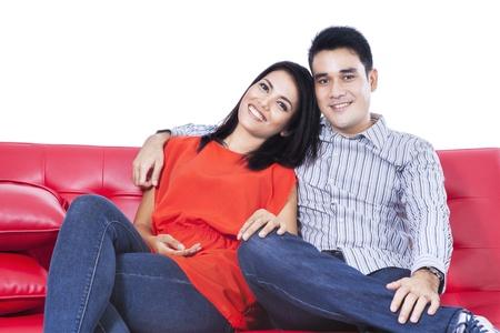 esposas: Pareja feliz descansando en un sof� de color rojo sobre fondo blanco