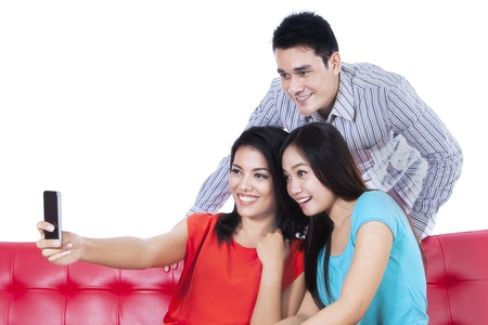 Three young friends taking photo by mobile phone on white background Stock Photo - 22114571