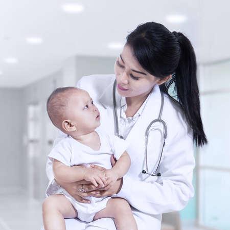 bebe enfermo: Pediatra de sexo femenino joven con un beb� en el hospital