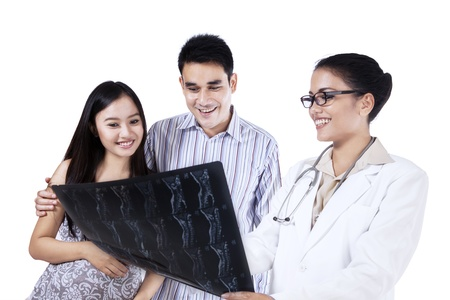 A female doctor showing x-ray to young couple isolated on white background photo