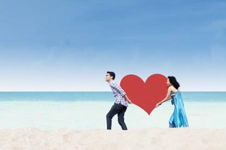 apporter: Happy couple asiatique apporter d�coupe du c?ur � la plage