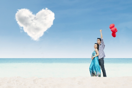 hands holding heart: Asian couple holding balloons while enjoying beach landscape under love cloud