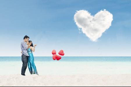 luna de miel: Hermosa joven con globos de corazón en la playa bajo las nubes del amor