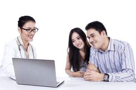 indonesian woman: Diagn�stico m�dico explicar a los pacientes con la computadora port�til en la oficina Foto de archivo