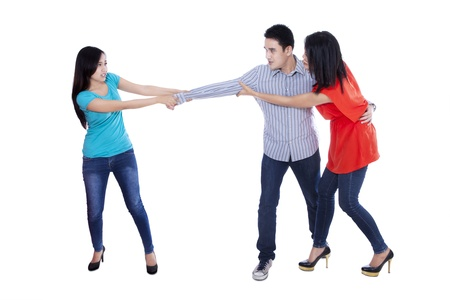 Two beautiful woman fighting over handsome man, isolated over white background photo