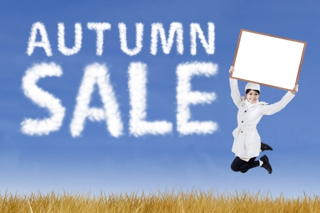 Autumn sale concept  woman with blank board jumping outdoor photo