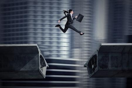 obstaculo: Empresaria asiática joven con la cartera que salta sobre un hueco en el puente