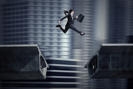 cliff: Young asian businesswoman with briefcase jumping over a gap in the bridge