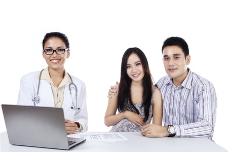Doctor with laptop and happy asian couple in doctor photo