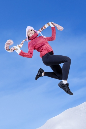 flying woman: Happy woman in winter dress jumping on blue sky background