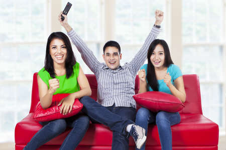 red sofa: Happy young teenager watching football on tv at home