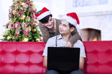 Romantic couple buying christmas gift online at home photo