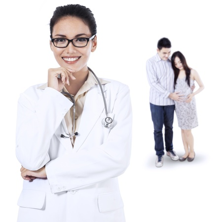 Smiling female doctor in front of a pregnant woman and her husband on white background photo