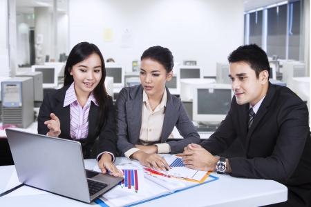 dolgozó: Három ázsiai üzleti csapat dolgozik a laptop az irodában Stock fotó