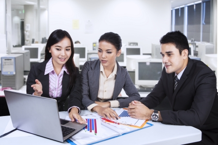 Three asian business team working with laptop at office Stock Photo