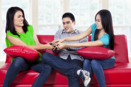 Three asian teenager fighting for a remote control at home Stock Photo - 22153864