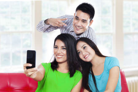 Three teenagers take a picture with mobile phone at home photo