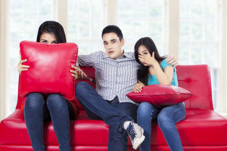 Three young teenagers watching TV a horror movie and they are scared photo