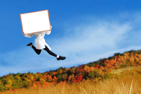 Woman jumping with holding blank board at autumn day photo