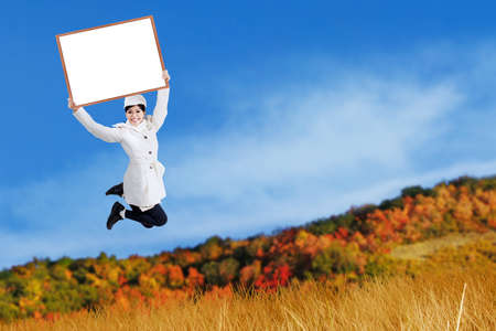 Young woman jumping with holding blank board at autumn day photo