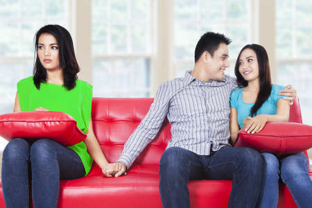 Beautiful young woman holding hands with man sitting near his girlfriend at home photo