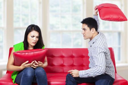 Angry couple on red sofa fighting with pillow in the living room Stock Photo - 22173042