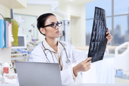 Asian female doctor holding x-ray results and using her laptop computer at clinic photo