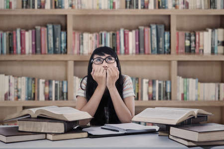 Asian female student anxious about the exam while studying at library photo