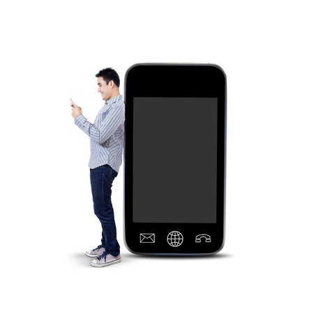 adult texting: Asian man using a mobile phone and standing next to big smartphone isolated on white background