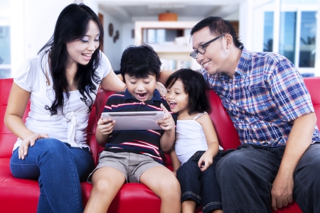 family asia: Family using digital table to browse the internet Stock Photo